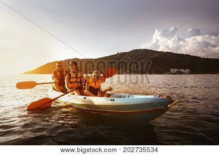 Family of father mother and young son kayaking at sea bay at sunset time. Space for text