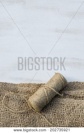 Skein jute twine and burlap on a wooden background. Rustic style. Selective focus.