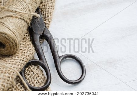 Old scissors skein jute twine and burlap on a wooden background. Rustic style. Selective focus.