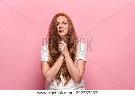 The young beautiful woman is offended, on a pink studio background
