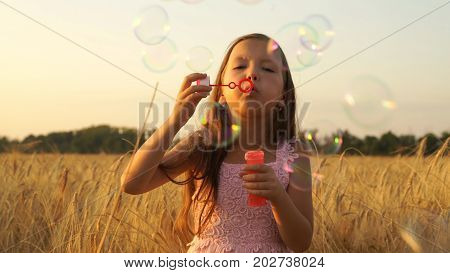 girl walks in the field and blows bubbles