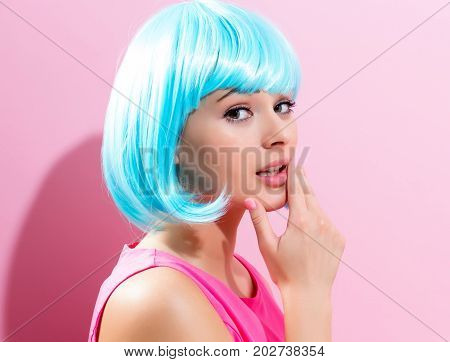 Beautiful woman in makeup with a bright blue wig on a pink background