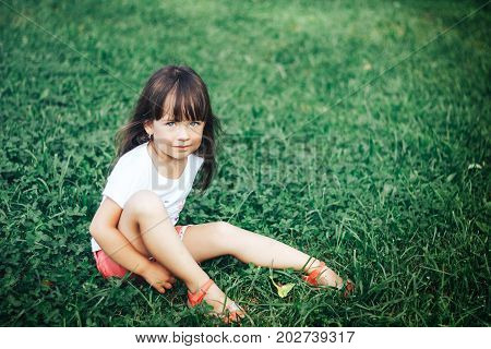 Adorable brunette little girl with very long hair sitting on grass in park