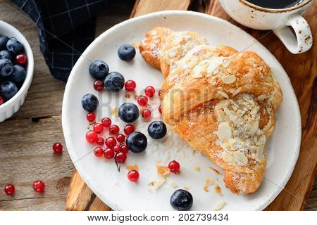Fresh croissant, blueberries and red currants on white plate. Continental breakfast. Horizontal composition