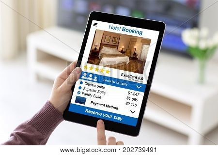 Female hands holding tablet with app hotel booking screen in room home