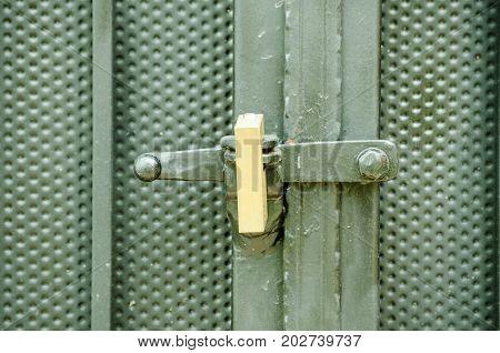 Golden padlock keeping locked black metal door