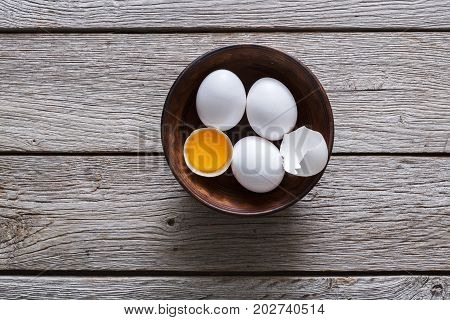 Fresh chicken white home eggs with cracked eggshell and yolk in bowl at rustic wood table. Top view with copy space. Rural still life, natural healthy food and organic farming concept.