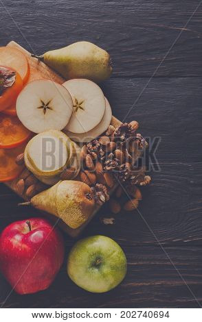 Healthy food - wood board with cut organic raw fruits on dark wooden background. Sliced ingredients for fruit salad or snack - apple, pear, nuts, persimmon, top view, copy space