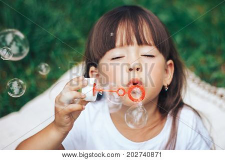 Girl with long hair blowing soap bubble at the camera and close her eyes
