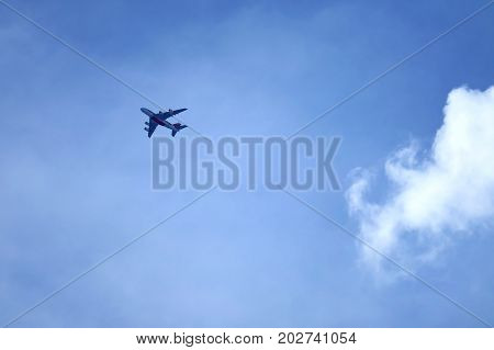 Flying airplane on blue sky with pure white cumulus cloud, Babgkok, Thailand, 11th August 2017