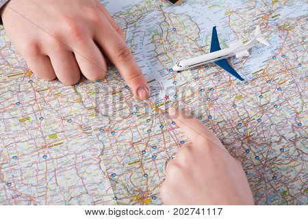 Couple planning trip to Chicago, USA, pointing on this city on map. Travel background with accessories