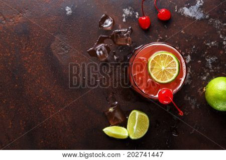 Red cocktail on brown background. Refreshing alcohol drink with tequila, citrus juice, lime and maraschino cherry on marbled table with melting ice and dices of refined sugar, copy space, top view
