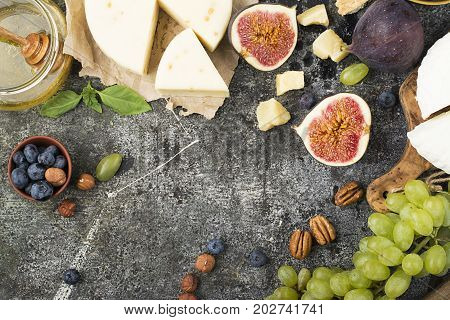 Cheese board for snacks, tricks, meetings with friends, on a gray stone background: assorted cheeses, young cheese, parmesan, cheese with fenugreek, figs, nuts, honey, grapes Top View