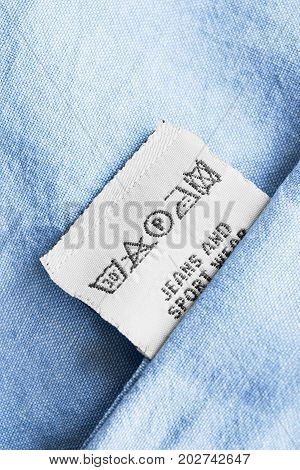Washing instructions clothes label on blue cotton as a background