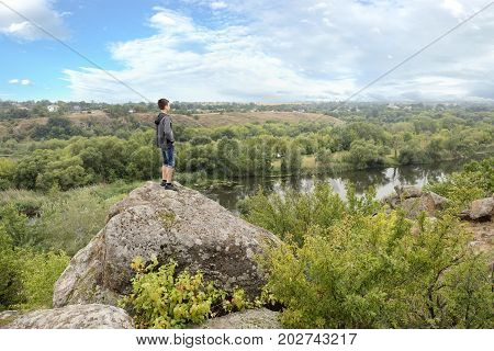The teenager stands on top of a large stone boulder on the bank of the South Bug River and looks at the river below. The river Southern Bug in the summer - river flow rocky shores bright green vegetation and a cloudy blue sky