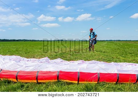 Young male paraglider waiting with parachute in meadow