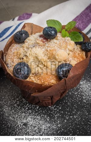 Blueberry muffins with powdered sugar and fresh berries.