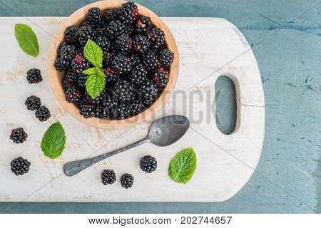 Bowl with and blackberries and mint leaves on a old wooden background
