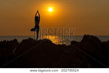 Silhouette young woman lifestyle exercising vital meditate and practicing yoga on the beach at sunset. Healthy Concept.
