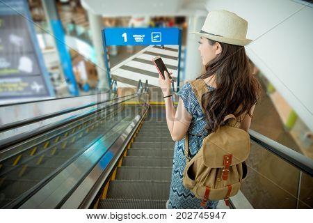 Smiling Female Traveler Using Mobile Smartphone