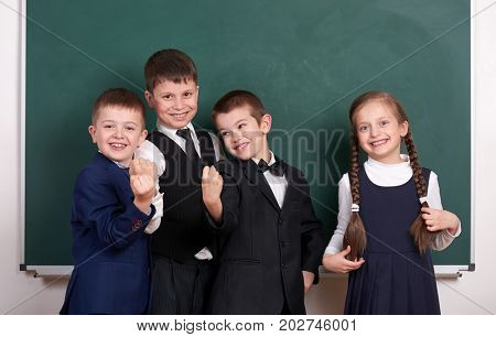 group pupil as a gang show knuckle, posing near blank chalkboard background, grimacing and emotions, friendshp and education concept