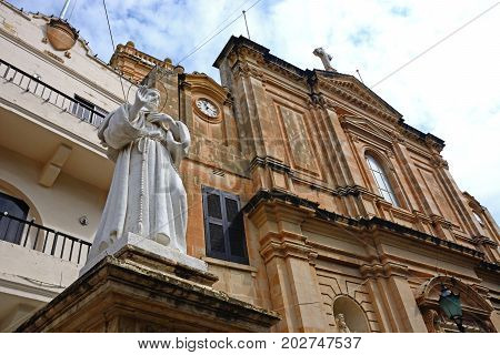 Front view of the Parish church of our lady of sorrows with a statue in the foreground Bugibba Malta Europe.