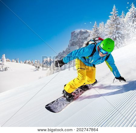 Active man snowboarder riding on slope, snowboarding closeup.