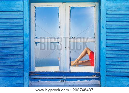 Beautiful vintage Greek window with blue shutters on a white wall. Typical Greek picture.