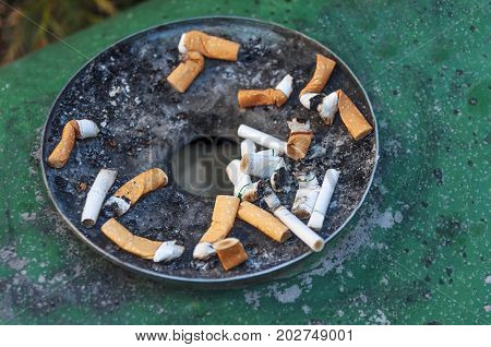 Cigarettes in outdoors green rusty ashtray close
