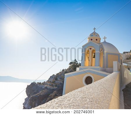 Beautiful yellow church dome on the edge of the town of Fira on Santorini island, Greece.