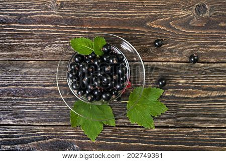 A glass cup with ripe forest berries. Large black currant berries. Harvest of berries on the farm. Top view.
