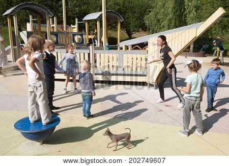 MOSCOW RUSSIA - SEPTEMBER 1 2017: Children and young woman trainer doing gymnastics exercises on playground in