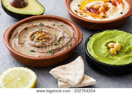 Different hummus bowls. Chickpea hummus, avocado hummus and lentils hummus on gray stone