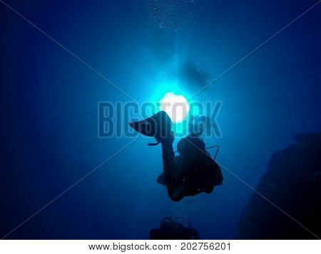 Scuba Divers Silhouette Against Sun. Group of scuba divers ascending.