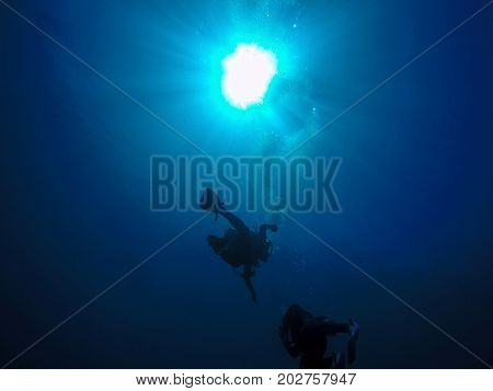Scuba Divers And Air Bubbles Against The Sunlight