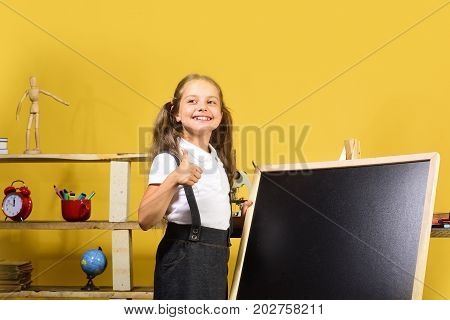 Kid And School Supplies, Yellow Background. Schoolgirl With Cheerful Face
