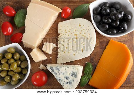 Delicacy. Food composition - different types of cheeses olives and tomatoes.