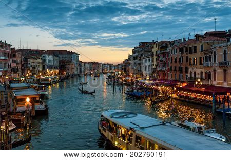 Grand Canal with tourist motor boat and gondolas at night in Venice, Italy. Grand Canal is one of the major water-traffic corridors and tourist attraction in Venice.