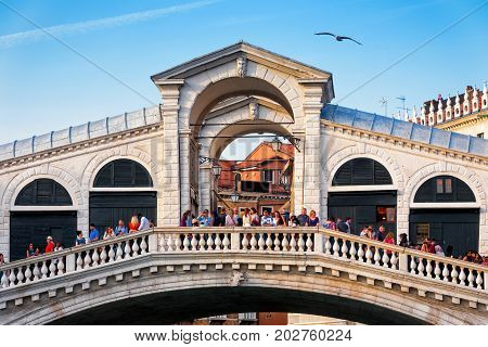 Venice, Italy - May 18, 2017: The old Rialto Bridge with many tourists. Rialto Bridge (Ponte di Rialto) is over the Grand Canal and one of the main tourist attractions of Venice.