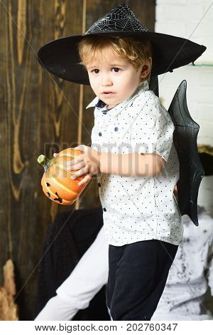 Kid With Scared Faces In Witch Hats Plays With Pumpkins
