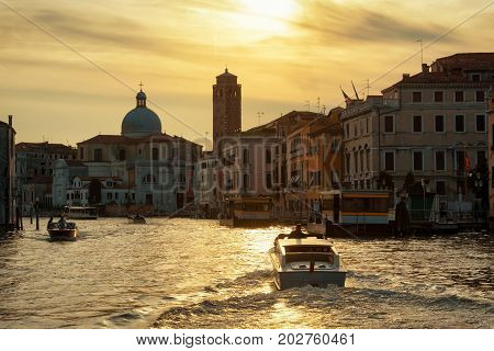 Water taxis are sailing along the Grand Canal at sunset in Venice, Italy. Grand Canal is one of the major water-traffic corridors in Venice.