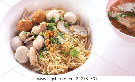 Egg noodle dry Asian food zoom in see detail Have fish and pork ball parsley green onions sliced bone soup shrimp dumplings in white plastic bowls isolate on white background has copy space.