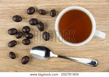 Scattered Peanuts In Cacao Powder, Tea And Teaspoon On Table