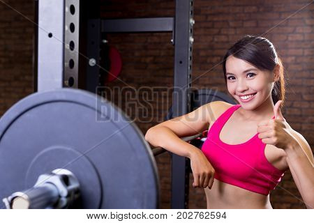 sport woman thumb up with barbell in the gym