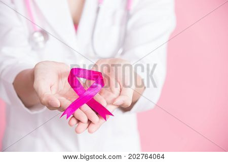close up doctor hold pink ribbon with breast cancer prevent concept