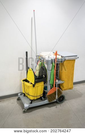 Cleaning service cart full of supplies and equipment for professional cleaner against white wall.