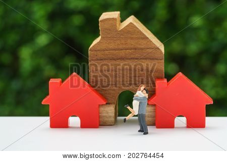 Miniature happy couple family standing with wooden house as property or financial mortgage plan concept.