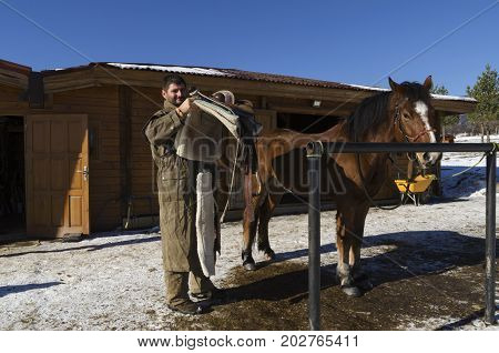 Man and horse Man taking off his saddle