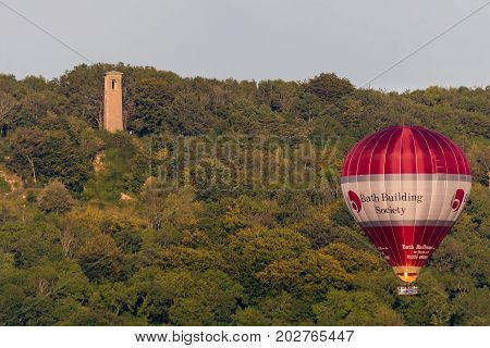 BATH UK - 28 AUG 2017 Bath Building Society hot air balloon with passengers. Liveried red and white balloon carrying large number of people in front of Brown's Folly tower