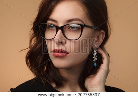 Beautiful brunette woman wearing glasses earrings touching hair looking away.